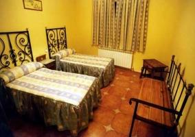 Dormitorio con camas individuales y banco