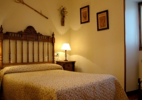 Habitación de matrimonio con cabecero de madera tallada