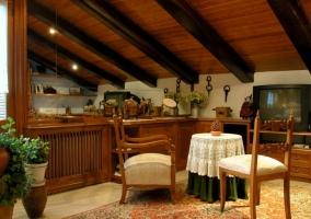 Zona de estar de la buhardilla con mesa y tele