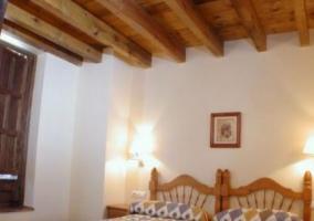 Dormitorio con camas individuales y tablones de madera en el techo