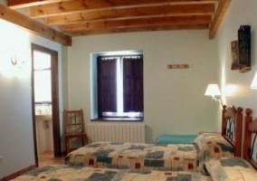 Dormitorio triple con dos camas y entrada al aseo