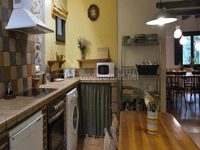 Cocina realizada en ladrillo, azulejos y pintura amarilla en la casa rural