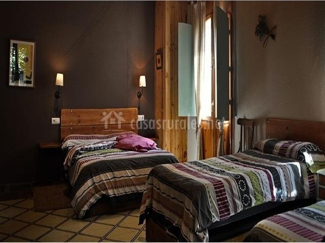 Dormitorio triple con pared oscura y colchas de detalles geométricos en la casa rural
