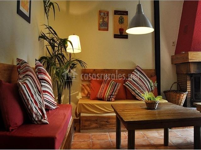 Saloncito con sofás burdeos, chimenea y mesita de centro de la casa rural