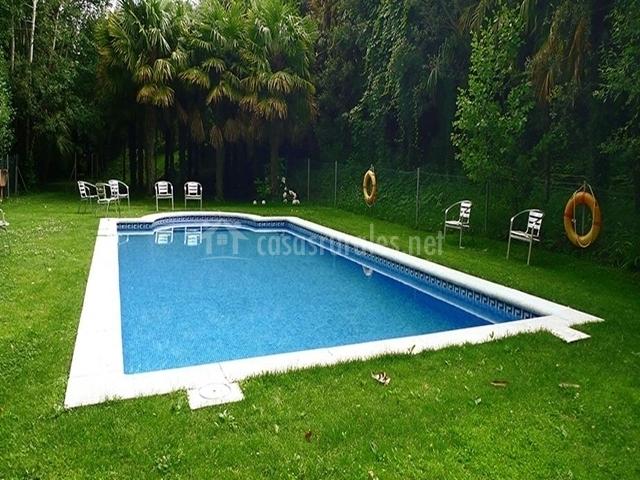 Vista de la piscina de la casa rural rodeada por un amplio césped y sillas