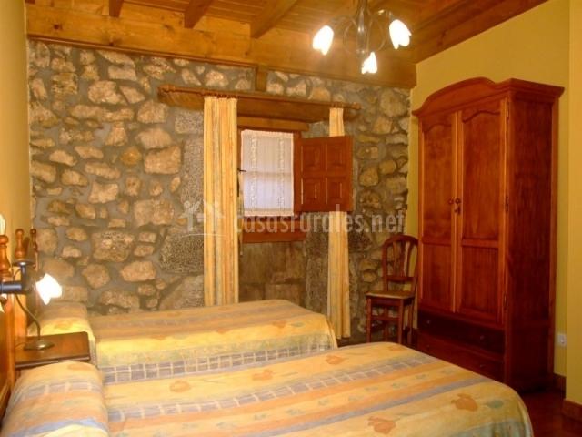 Dormitorio con pared de piedras y dos camas