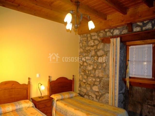 Dormitorio con techo de madera y dos camas