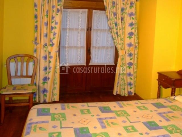 Dormitorio doble con paredes amarillas