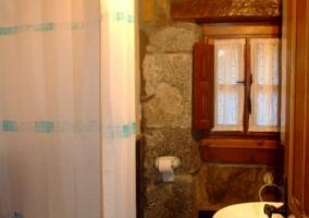 Aseo con ducha y pared de piedra