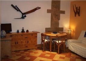 Salón de la casa rural con televisión y mesa