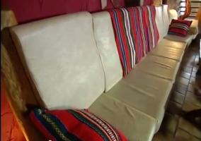Detalle del sofá blanco con mantas rojas