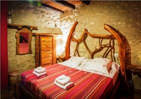 Dormitorio de matrimonio con cabecero hecho con troncos y paredes de piedra