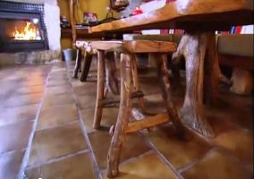 Mesa de madera con taburetes y chimenea