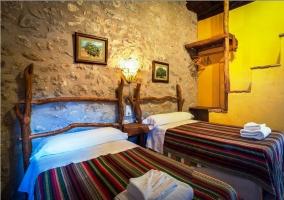 Dormitorio doble con pared de piedra y cabecero de troncos