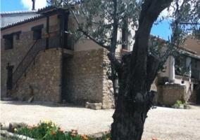 Vistas de la fachada de la casa rural con árbol frutal
