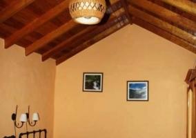 Dormitorio con dos camas individuales de rayas verdes y techos abuhardillados