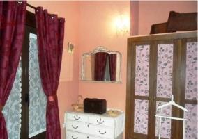 Detalle del dormitorio rosa y granate de la casa rural