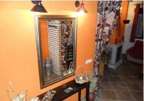 Espejo del salón de la casa rural con marco plateado