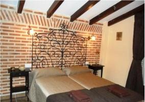 Dormitorio de la casa rural con camas unidas y cabecero de forja
