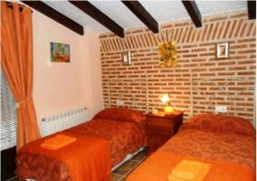 Dormitorio naranja con dos camas en la casa rural