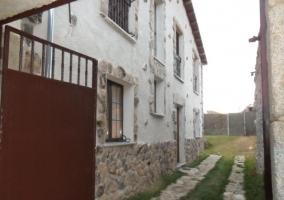 Fachada trasera de la casa rural con portón abierto