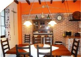 Mesa de comedor de la casa rural con la cocina al fondo