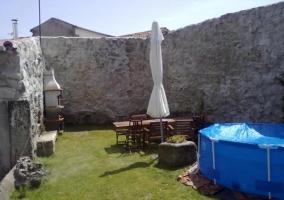Rincón del jardín de la casa rural con piscina hinchable, sombrilla cerrada y barbacoa