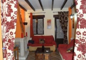 Salón con chimenea de la casa rural y vistosas cortinas