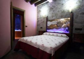 Dormitorio doble con cama de matrimonio en tonos morados y madera