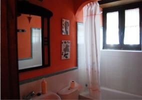 Cuarto de baño con bañera y paredes naranjas