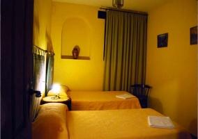Dormitorio con dos camas individuales con paredes y edredones amarillos