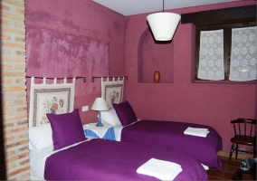 Dormitorio con dos camas individuales moradas