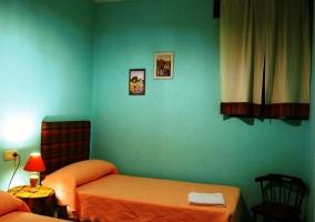 Dormitorio con dos camas individuales naranjas con paredes azules