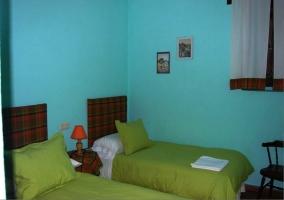 Dormitorio con dos camas individuales verdes y paredes azules