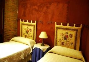 Dormitorio con dos camas individuales y cabeceros de tela con flores