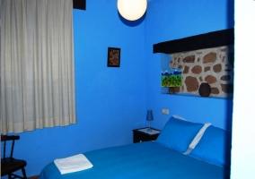 Dormitorio de matrimonio con edreóno y paredes azules