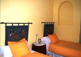 Dormitorio doble con dos camas individuales naranjas y cabeceros con motivos egipcios