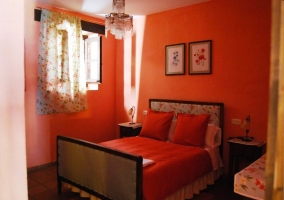 Dormitorio doble con paredes rojas y cortinas