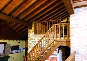 Escaleras, pared de ladrillo y piedra y techo abuhardillado