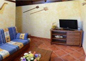 Salón de la casa rural con televisión y sofás