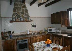 Cocina tradicional de la casa rural andaluza con mesa y sillas de madera