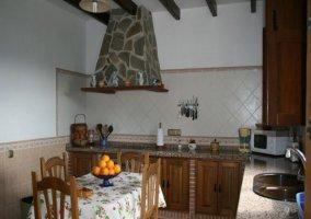 Cocina con mesita para comer decorada con  mantel de cerezas en la casa rural