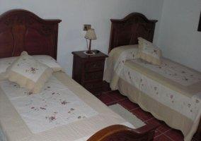 Dormitorio con dos camas individualescon colchas de flores en la casa rural