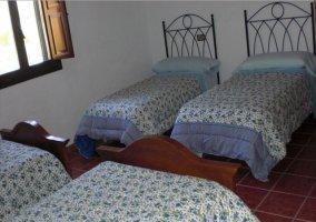 Dormitorio cuatriple con colchas de flores en la casa rural