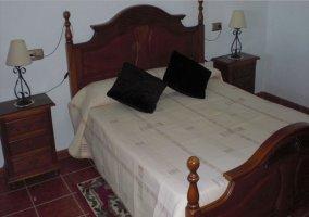 Dormitorio matrimonial con cabecero de madera en la casa rural