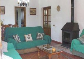 Sofás verdes alrededor de mesita de centro y detalle de la chimenea en la casa rural