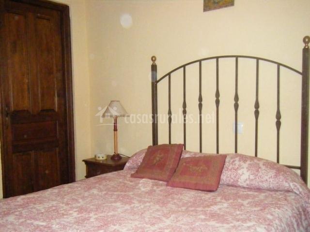 Dormitorio de matrimonio con cabecero de forja en la casa rural