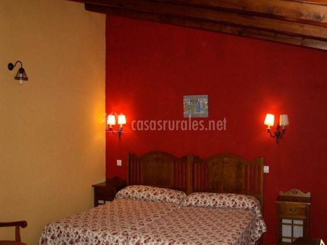 Dormitorio doble del alojamiento rural en tonos rojos y madera en el techo