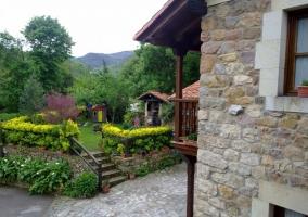 Jardin de la casa rural con zona de cesped para comer al aire libre y barbacoa de lena