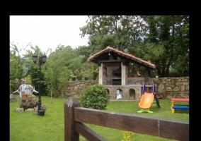Zona del jardín dedicada a la barbacoa de lena y pequenos juegos infantiles de colores para los mas pequenos